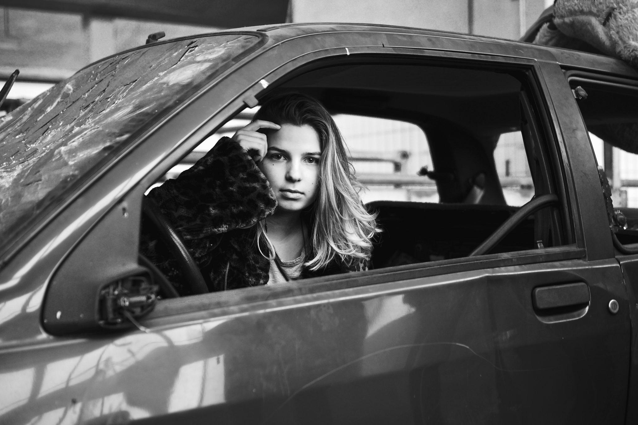 Ein kaputtes Auto mit eingeschlagenen Fenstern in dem ein Model von der Fotografin Felicitas Jander sitzt und sich durch die Haare faesst.