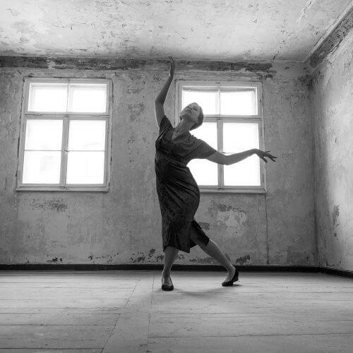 Das Model und Schauspielerin Anna Mariani nimmt eine tanzende Form ein und steht in einem alten leeren Raum.