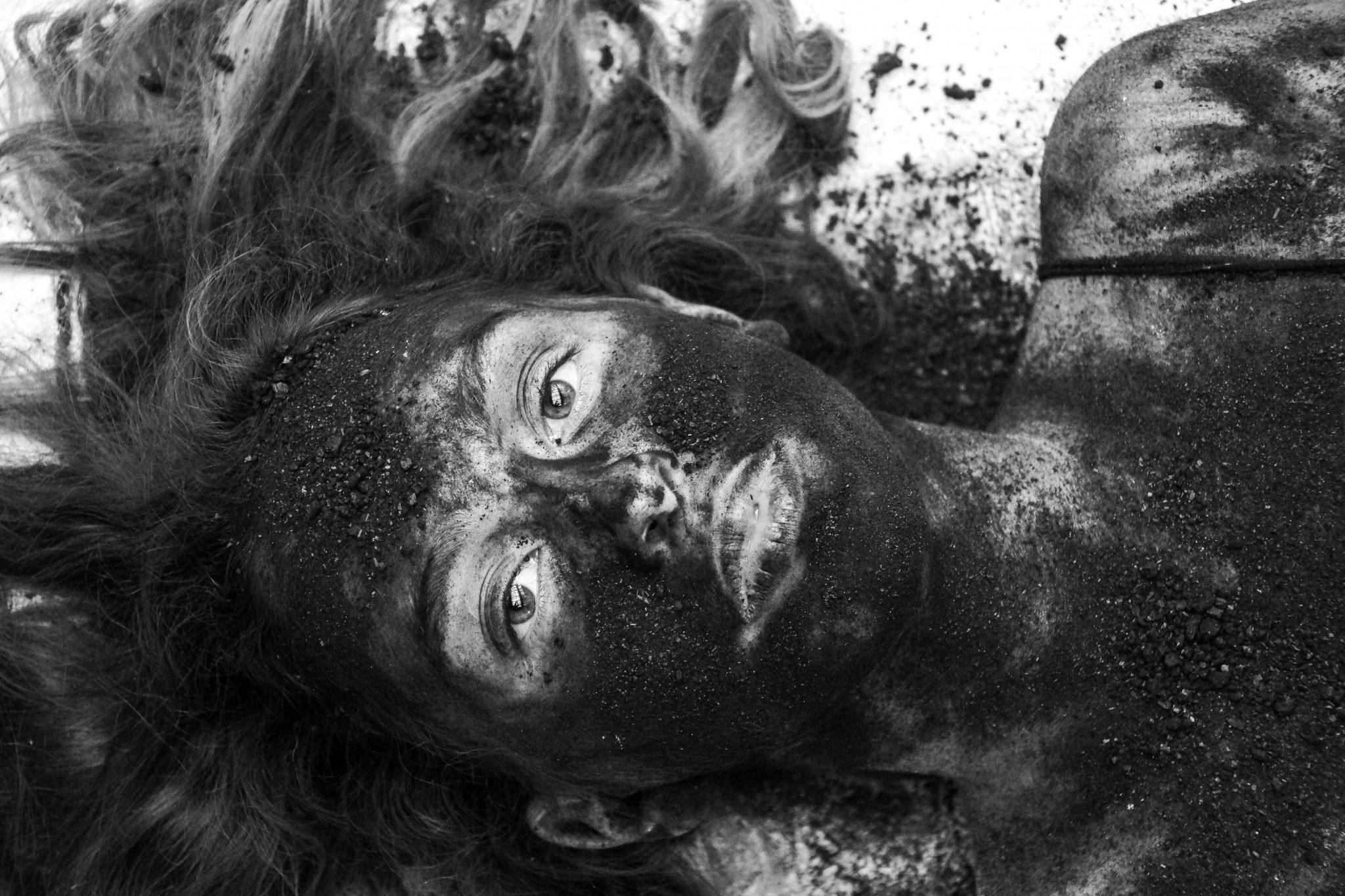 Ein weibliches Gesicht mit Kohle beschmiert und offenen Haaren liegt am Boden der verlassenen Bowlinghalle.