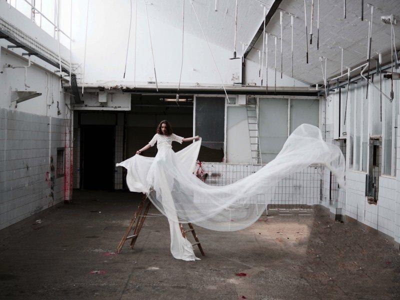In einer verlassenen Fleischerhalle steht ein Model in einem weissen Kleid auf einer Leiter.