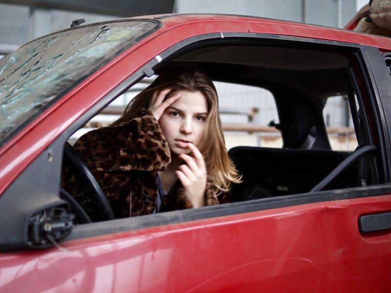 Ein kaputtes Auto mit eingeschlagenen Fenstern in dem ein Model von der Fotografin Felicitas Jander sitzt und ihre Lippen beruehrt.