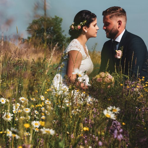 Hochzeitsfoto von dem Ehepaar Madeline und Michael, waehrend sie in einer Blumenwiese sitzen.