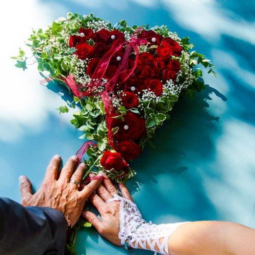 Die Haende des Brautpaares auf einer Motorhaube abgelegt und darauf ein Blumenstrauss aus roten Rosen in Form eines Herzens angeordnet.