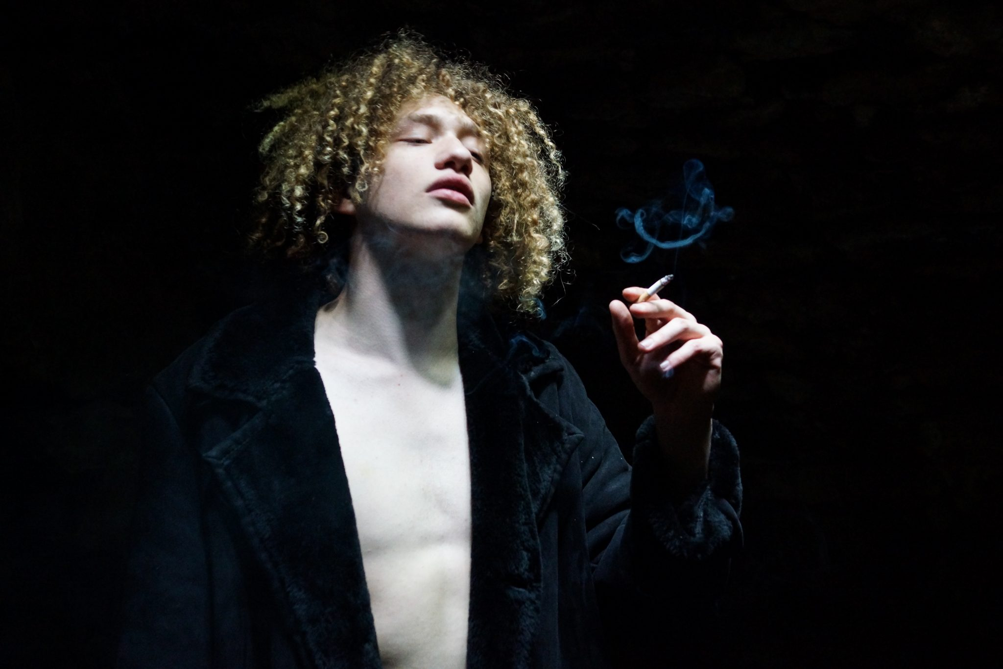 Ein Mann namens Johnny in einem schwarzen Mantel raucht eine Zigarette.