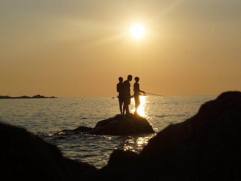 Korsika mit ihrer eleganten Kueste. Drei junge Maenner stehen auf einem Stein und Angeln im Sonnenuntergang.