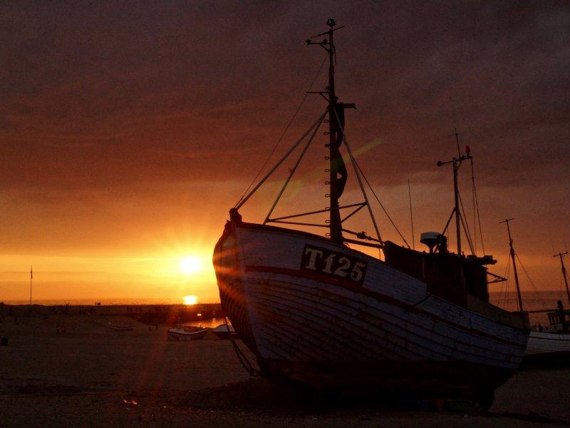 Ein gestrandetes Boot mit dem Namen T125 wurde im Sonnenuntergang fotografiert.