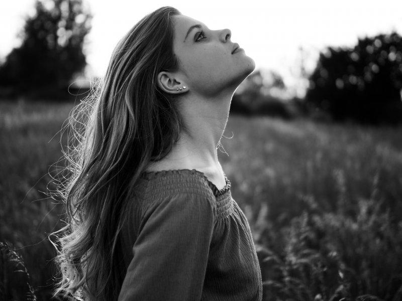 Lilli Schmidt in einer schwarz-weiss Aufnahme. Sie steht in einem Feld und sieht in die Luft.