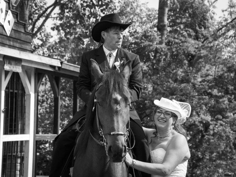 Nur das Brautpaar ist zu sehen. Der Braeutigam sitzt auf einem Pferd, waehrend seine Braut neben ihm steht.