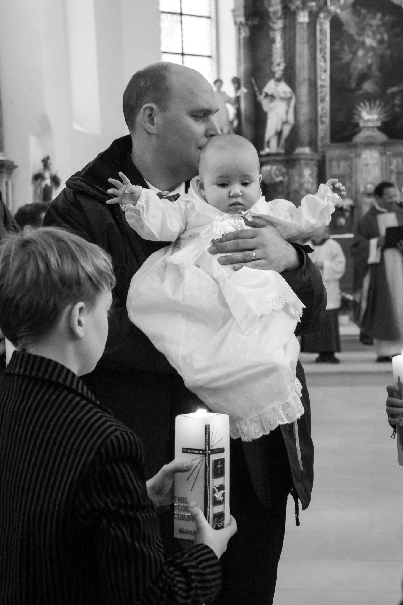 Das Taufkind gehalten von seinem Vater in einem prächtigen weissen Kleidchen.