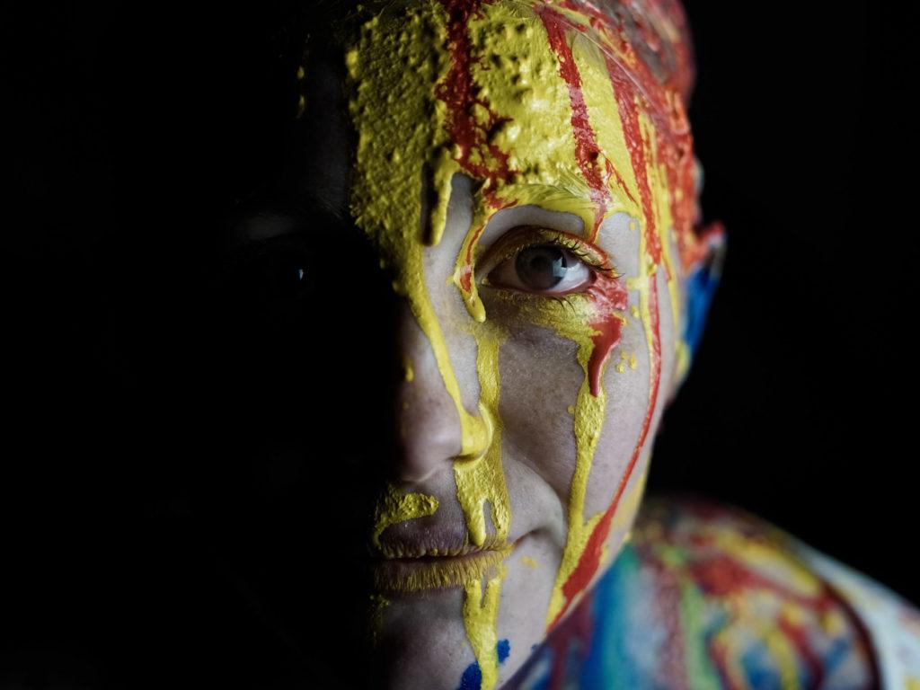 Gesicht einer Frau mit blauer, gelber und roter Farbe beschmiert. In Wuerzburg von Felicitas Jander fotografiertes Portrait.