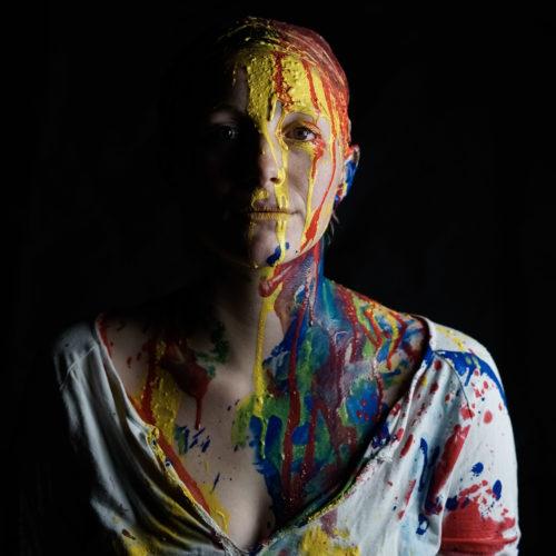 Gesicht einer Frau mit blauer, gelber und roter Farbe beschmiert. Aufnahme in wuerzbuger Umgebung in einem Studio fotografiert von Felicitas Jander. Sehen Sie mehr im gesamten Portfoliobeitrag.
