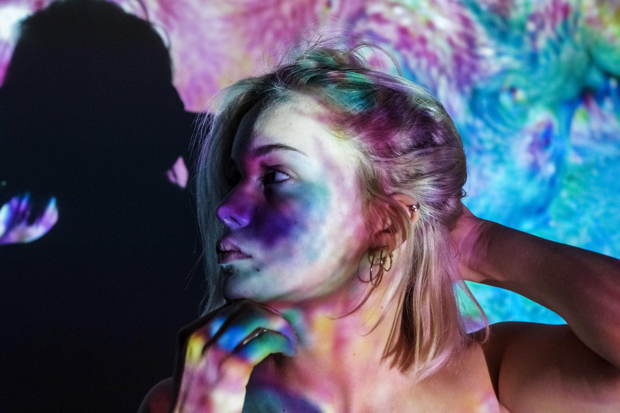 Ein Muster aus verschwommenen Farben wird durch einen Beamer auf das Model Friedel beschienen. Der Kopf vom Model Friedel ist zur Seite geneigt und zeigt die Farben auf Ihrer Wange.
